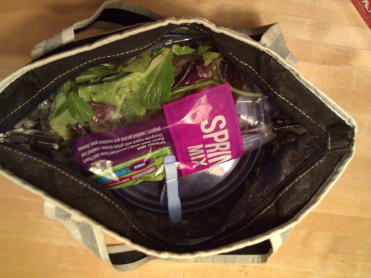 Stuff in lunchbox with lettuce or spinach and a paper plate